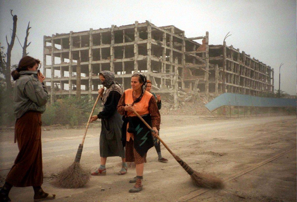 Reuters / Una donna cecena si copre il viso mentre cammina accanto ad un gruppo di donne in una strada abbandonata nel centro di Grozny, proprio accanto ad un palazzo distrutto dai bombardamenti durante la Prima Guerra Cecena, nel settembre 1996. L'Accordo di Khasavyurt decise la fine della Prima Guerra Cecena, nell'agosto 1996.