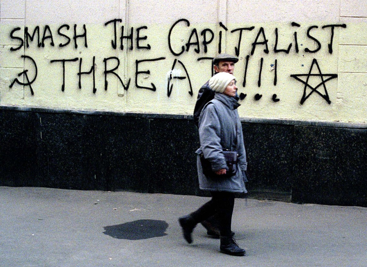 Reuters / Una coppia passeggia accanto ad alcuni graffiti nel centro di Mosca, nell'ottobre 1996. Alcune persone vennero colpite pesantemente dall'apertura dell'economia Russa ed erano nostalgici dell'era Sovietica.