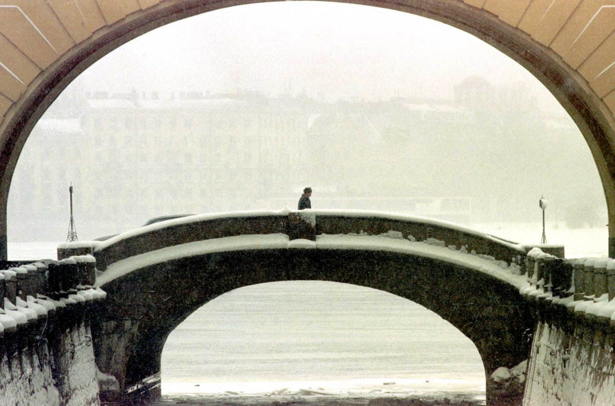Reuters / Un uomo attraversa un ponte nel centro di San Pietroburgo, aprile 1998.