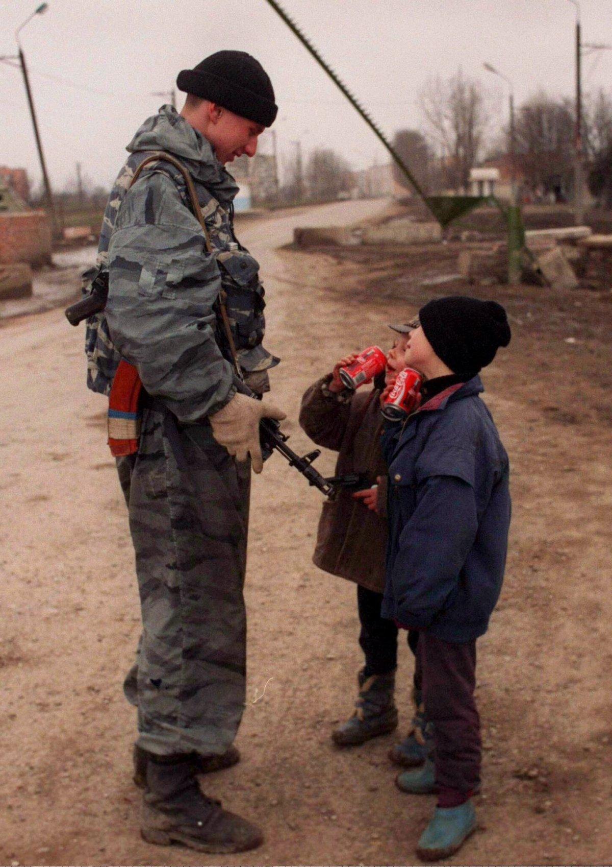 Reuters / Un soldato russo parla a dei bambini ceceni mentre bevono una Coca-Cola al check point vicino alla città di Grozny, marzo 1996