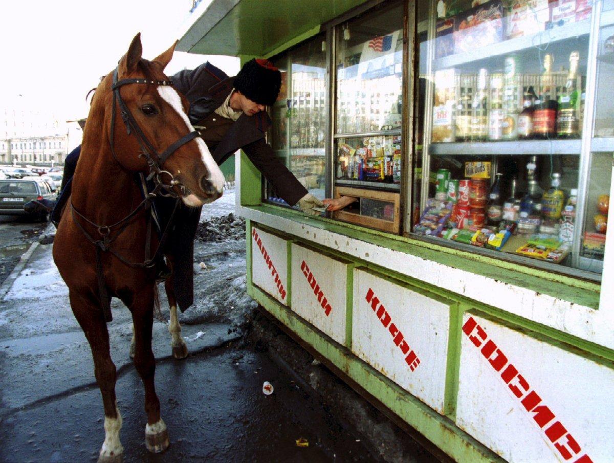 Reuters / Un Cosacco a cavallo compra una bottiglia di vodka da un chiosco in strada dopo aver partecipato al giorno di San Patrizio a Mosca. Questo evento, non certo tradizionale in Russia, fu promosso dal ministero degli esteri nel marzo 1994