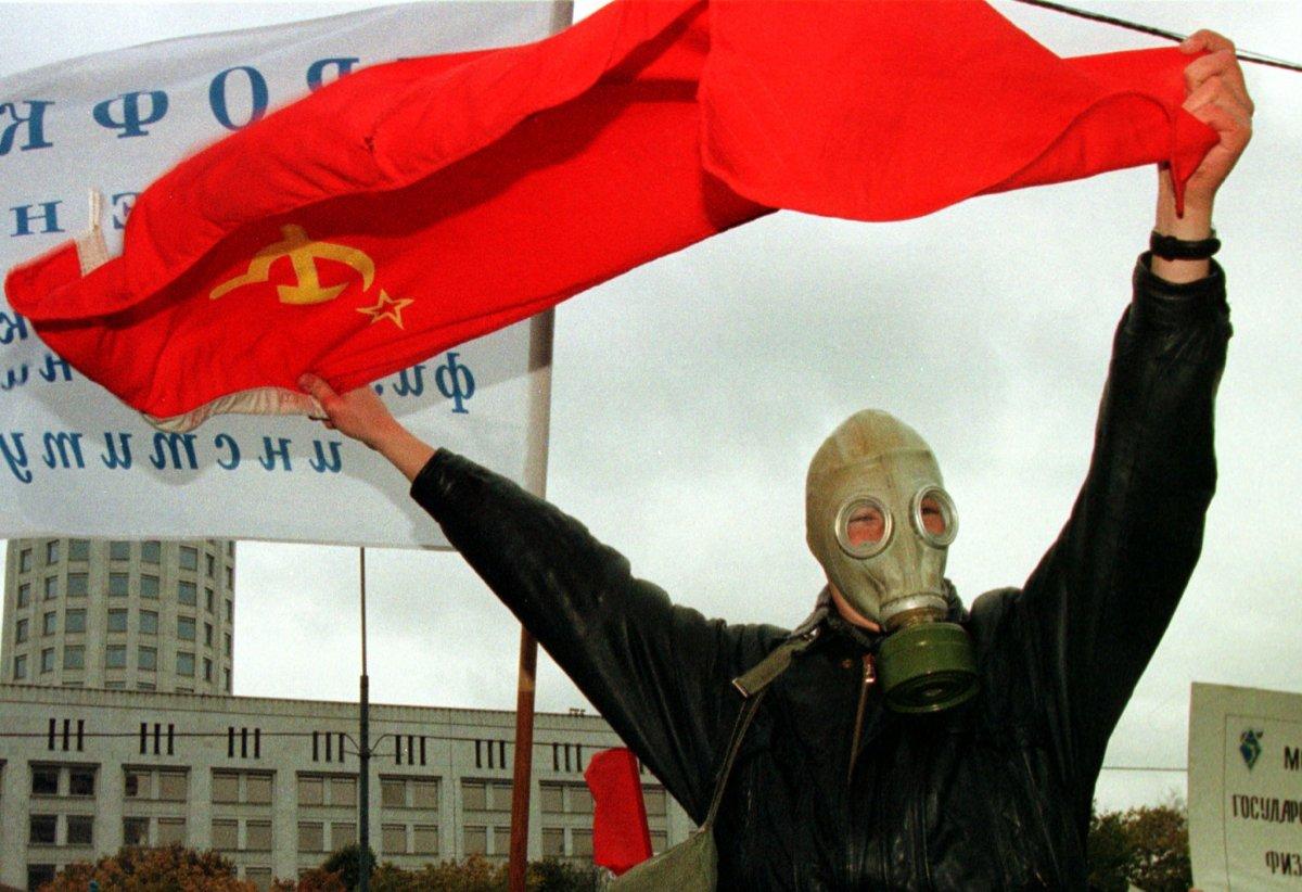 Reuters / Uno studente russo con una maschera anti-gas sventola una bandiera sovietica durante una manifestazione a Mosca, ottobre 1998.