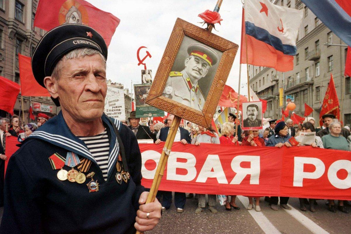 Reuters / Un veterano della Seconda Guerra Mondiale mostra un ritratto dell'ultimo dittatore sovietico Joseph Stalin durante una marcia per la celebrazione del Giorno della Vittoria, Mosca 9 maggio 1997.