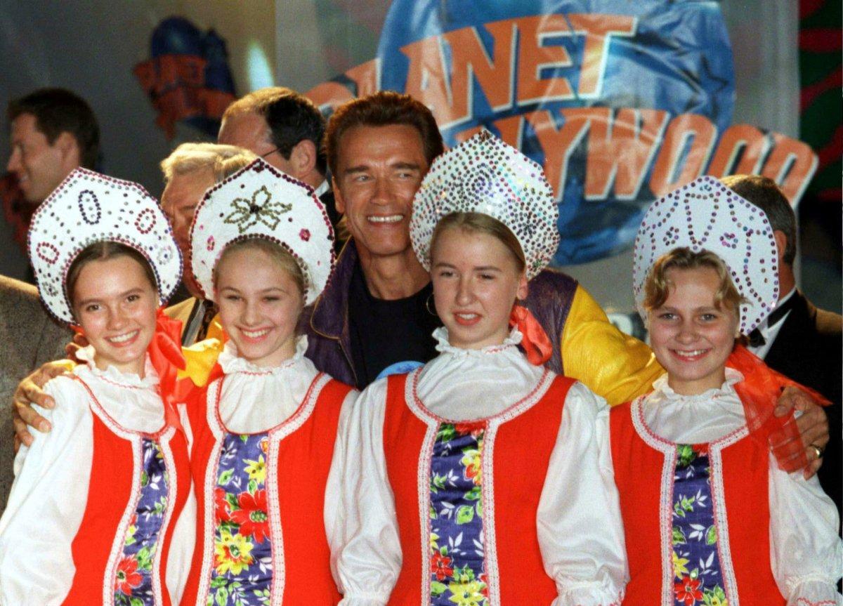 Reuters / Arnold Schwarzenegger posa con delle bambine russe vestite con gli abiti tradizionali durante la cerimonia al Planet Hollywood Cafe a Mosca, settembre 1996.