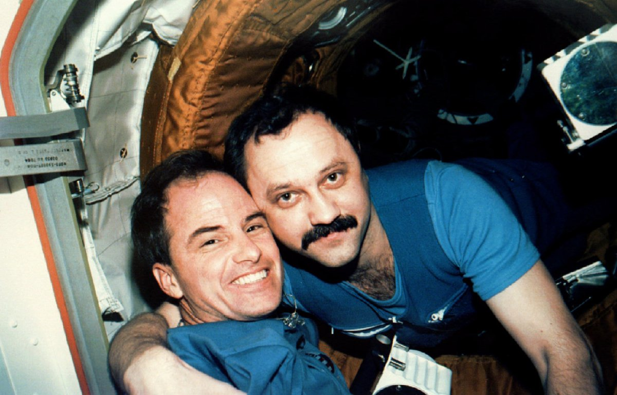 NASA-Reuters / L'astronauta Kevin Chilton, sulla sinistra, comandante della missione STS-76 riceve il saluto del cosmonauta russo Yuriy Usachov, ingegnere del Mir21, mentre lo space shuttle Atlantis si separa dal modulo Russo Mir nella stazione spaziale il 28 marzo 1996.