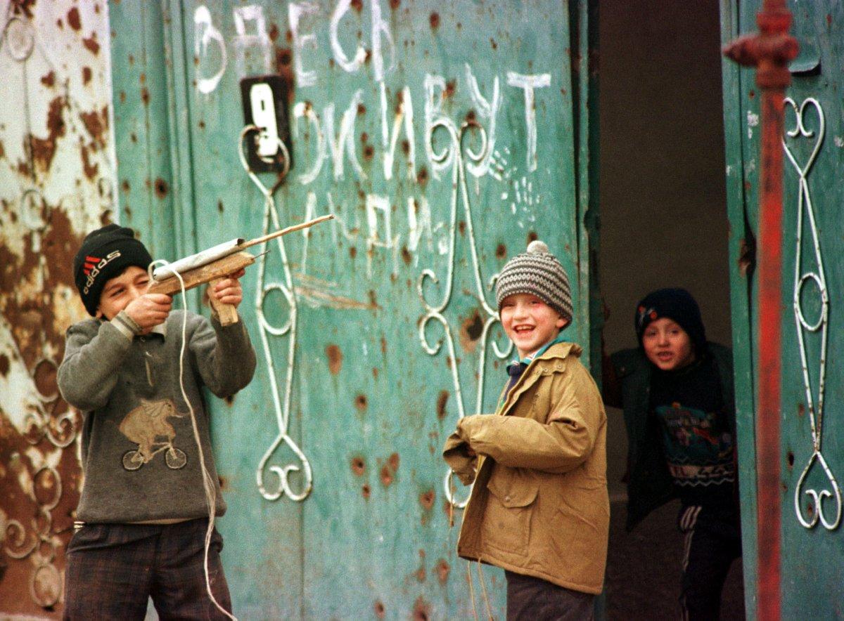 Reuters / Alcuni bambini ceceni si divertono con armi giocattolo nelle strade di Grozny, dicembre 1998. La Seconda Guerra Cecena era iniziata qualche mese prima, nell'agosto 1999.