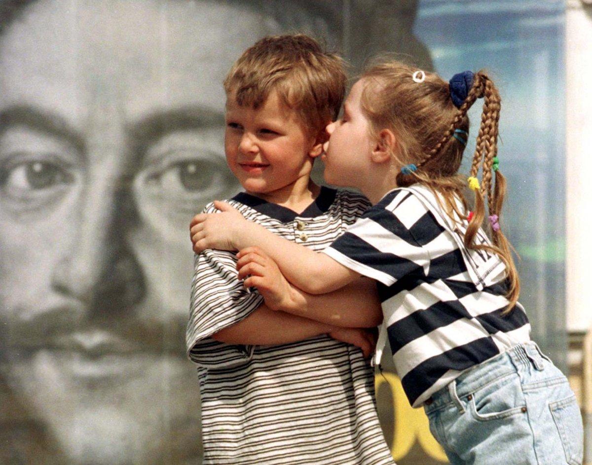 Reuters / Due bambini con alle spalle un poster di Pietro il Grande, 23 maggio 1999.