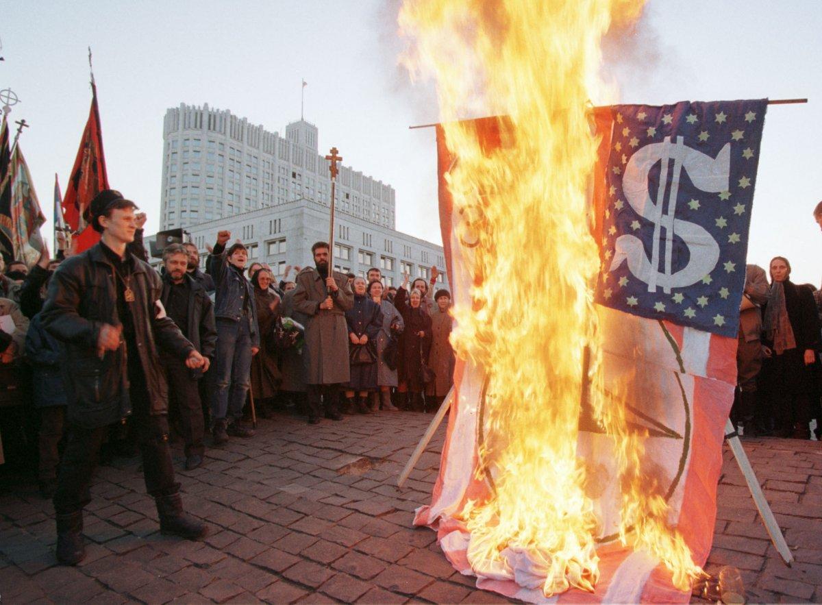 Reuters / Protestanti bruciano una bandiera di fronte al Parlamento, il 31 marzo 1999. La protesta, promossa da centinaia di cittadini, era contro i bombardamenti in Jugoslavia.