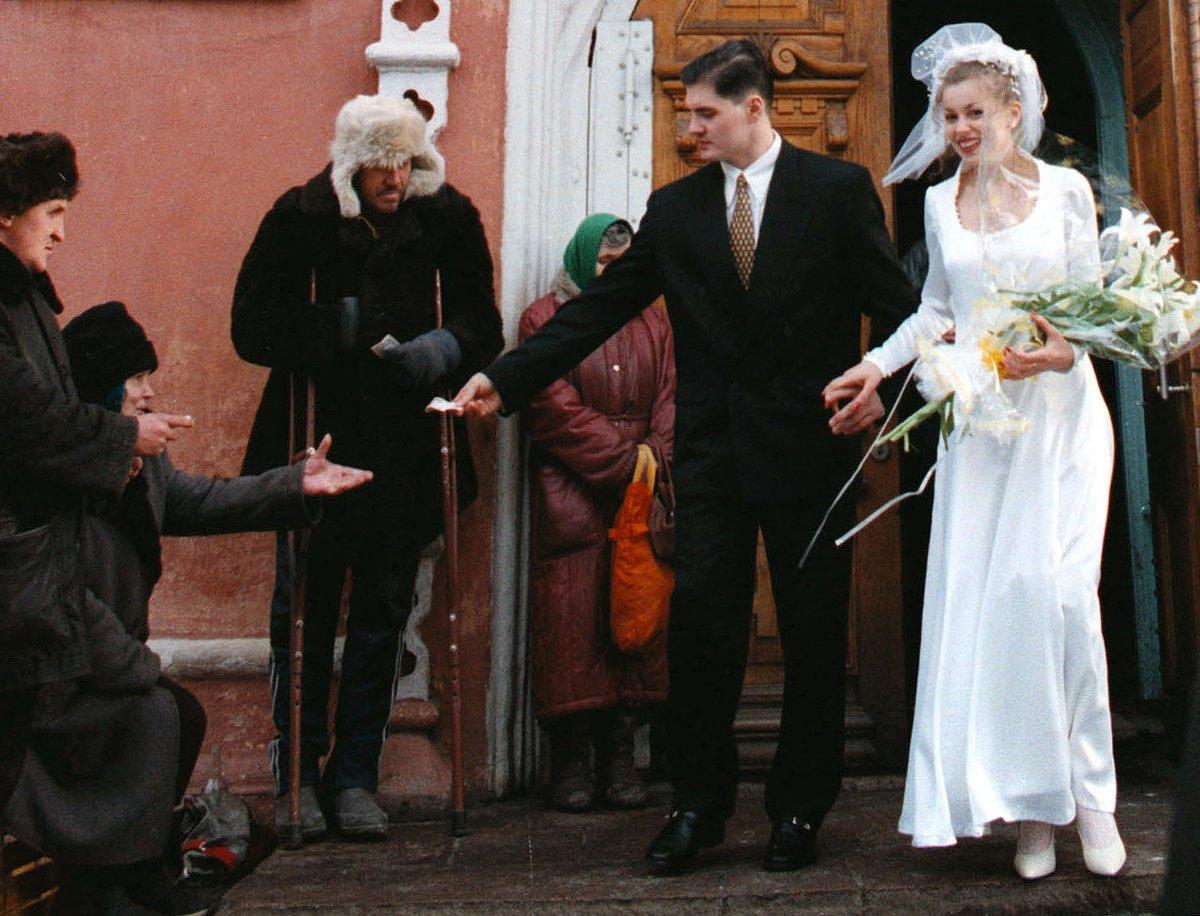 Reuters / Due sposini fanno l'elemosina mentre lasciano la chiesa nella città di Kasnoyarks, Siberia, ottobre 1998.