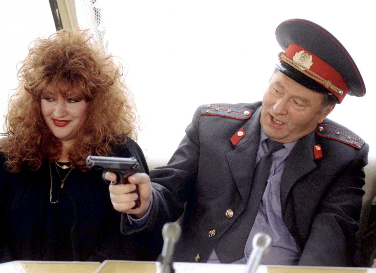 Reuters / Il politico russo Vladimir Zhirinovsky sorride mentre punta una pistola verso la cantante Alla Pugacheva durante una conferenza stampa il 7 dicembre 1996.