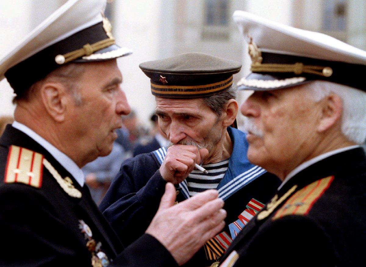 Reuters / Alcuni veterani russi discutono e un marinaio della Seconda guerra mondiale fuma una sigaretta mentre è attesa una manifestazione dinanzi al teatro Bolshoi nel giorno delle celebrazioni del Giorno della Vittoria, 9 maggio 1994