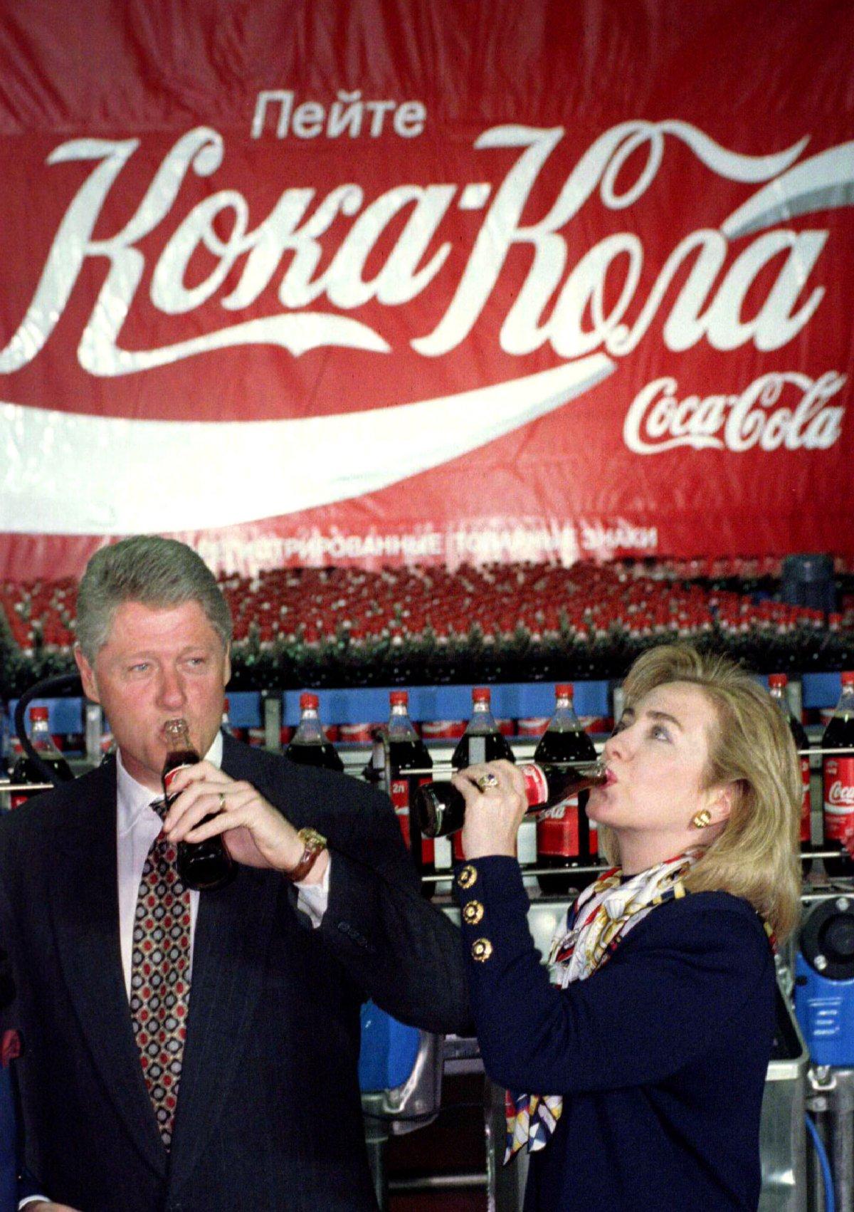 """Reuters / L'allora presidente Bill Clinton e Hillary Rodham Clinton bevono Coca-Cola durante la visita alla fabbrica Coca-Cola a Mosca nel maggio 1995, poco prima della visita di due giorni all'Ucraina. Lo striscione alle spalle recita """"bevete Coca-Cola"""" in lingua russa."""