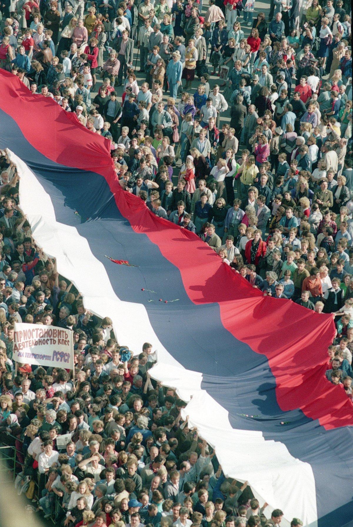 AP / Centinaia di moscoviti marciano verso la Piazza Rossa portando un'enorme bandiera tricolore per celebrare il fallimento del colpo di stato. 22 agosto 1991